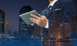 Double exposure of businessman using digital tablet with modern building and social media