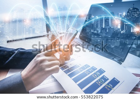 Double exposure of businessman using smart phone at office with city night background, network connection concept