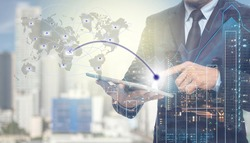 Double exposure of businessman using tablet for sending the email with cityscape and financial graph on blurred building background,Business Trading concept,Elements of this image furnished by NASA