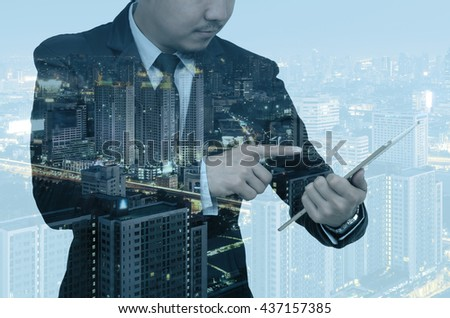 Double exposure of businessman using the tablet on cityscape background, Business real estate concept #437157385