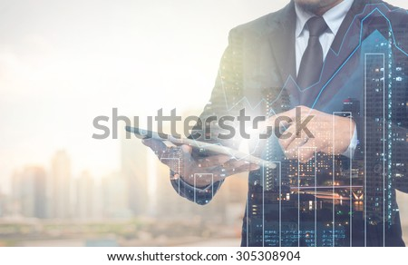 Double exposure of businessman using the tablet with cityscape and financial graph on blurred building background, Business Trading concept stock photo