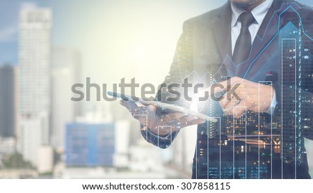 Double exposure of businessman using the tablet with cityscape and financial graph on blurred building background, Business Trading concept #307858115