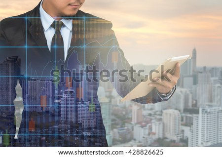 Double exposure of businessman using the tablet with cityscape and financial graph on blurred building background, Business Trading concept #428826625