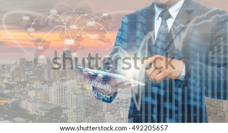 Double exposure of businessman using the tablet with Stock market chart on blurred building with connection and email background, Business Trading and connection concept #492205657