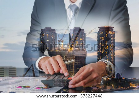 Double exposure of businessman working with calculator and construction crane and building in the evening, twilight as Worker, Commitment, Calculation and industrial concept