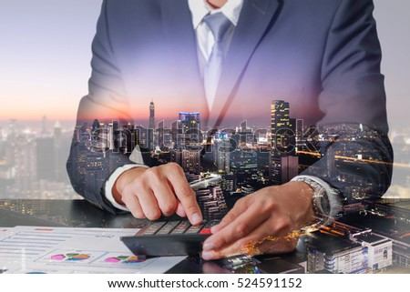 Double exposure of businessman working with calculator, cityscape, urban and street in the night or twilight as Worker, Commitment and Calculation concept #524591152