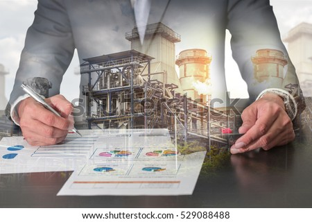 Double exposure of businessman working with document, calculator for analyze in the work, electric Generating Factory, Power Reactor and sunset as industrial, energy, analysis and commitment concept. #529088488