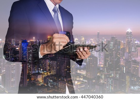 Double exposure of businessman working with tablet and night city as Communication and Commitment concept. #447040360