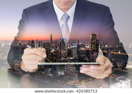 Double exposure of businessman working with tablet and night cityscape as technology and communication concept #426380713