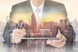 Double exposure of businessman working with tablet, cityscape and sunset as telecommunication and technology concept.