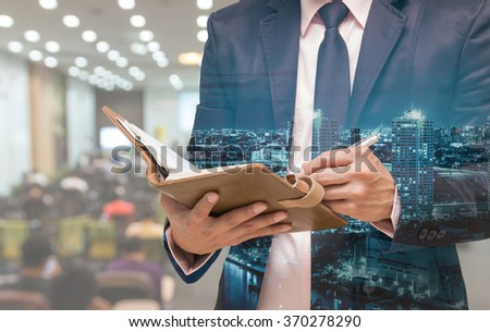 Double exposure of Businessman writing the note book on the Abstract blurred photo of conference hall or seminar room with attendee background