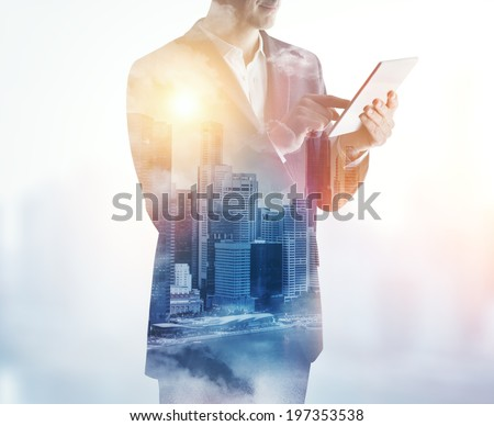 Double exposure of city and business man using digital tablet  stock photo
