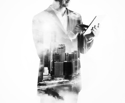 Double exposure of city and businessman using digital tablet