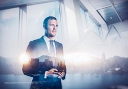 Double exposure of city and businessman using his smartphone