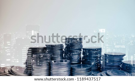 Double exposure of city and rows of coins for money, finance and business concept