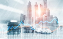 Double exposure of city and rows of coins with stock and financial graph on virtual screen. Business Investment concept.