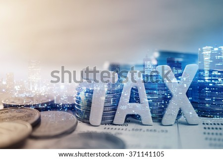 """Double exposure of city, """"tax"""" wooden text and rows of coins for finance and banking concept"""