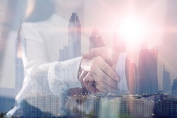 Double exposure of cityscape and business people shaking hands in office, closeup. Team work