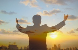 Double exposure of confident young businessman lifting his arms up to the sunrise sky facing the city. Religious belief, people feeling inspired and motivated concept.