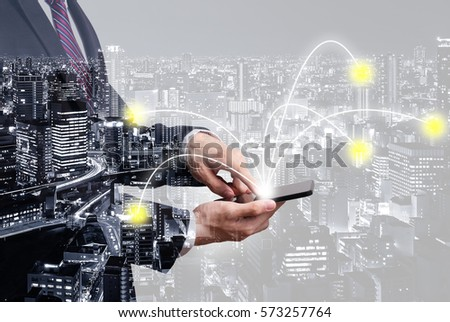 Double exposure of connectivity concept - businessman using smartphone with connected line with city overlay #573257764