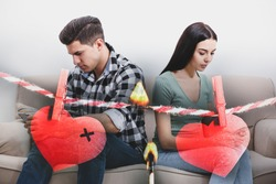 Double exposure of couple addicted to smartphones ignoring each other, red paper hearts on rope and burning match. Relationship problems