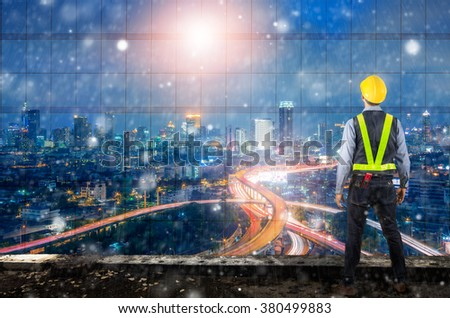 Double exposure of Engineer holding a yellow helmet for safety of the workers. A modern high-rise structures in the background with strom.