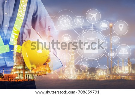 Double exposure of engineer holding yellow helmet for safety of the workers, Blurred Oil refinery background, Industry 4.0 concept.