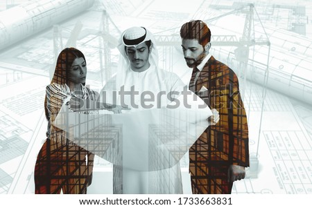 Double exposure of 2 Engineer with Arab businessman holding plan with buildings background.