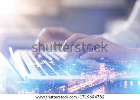 Double exposure of female programmer using laptop and cityscape, closeup