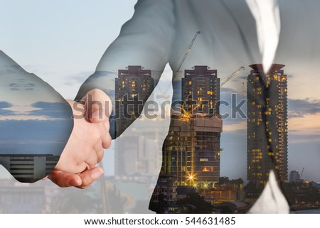 Double exposure of handshake, construction crane and building in the evening, twilight as business, relationship, partnership, commitment and industrial concept #544631485