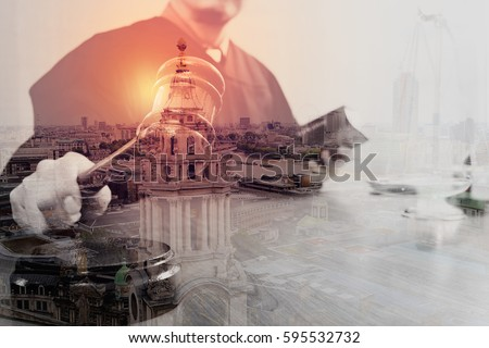 Double exposure of justice and law concept.Male judge in a courtroom with the gavel and working with holy book and brass scale on wood table with London city #595532732