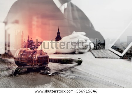 double exposure of justice and law concept.Male judge in a courtroom with the gavel,working with digital tablet computer docking keyboard on wood table,London architecture city