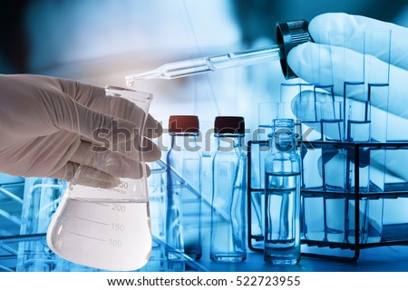 Double exposure of Laboratory pipette with drop of liquid over glass test tubes for an experiment in a science research lab , Laboratory research concept