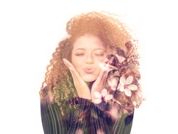 Double exposure of lovely woman giving kiss and beautiful cherry blossoms
