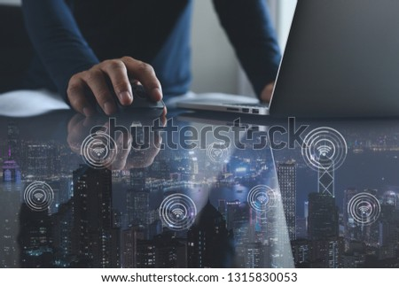 Double exposure of man programmer or software developer working on laptop computer and city with connecting dot technology of smart city. IoT Internet of Things, social media, wireless network concept