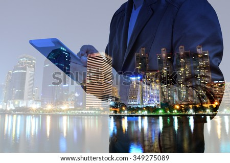 Double exposure of Night city and business man using digital tablet device as Business development concept. #349275089