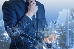 Double exposure of professional businessman touching smart phone with cityscape and financial / trading graph in Business trading and technology concept
