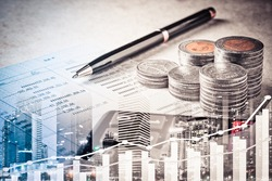 Double exposure of row of coins on account book,city and bar and graph interface in business,banking and finance concept