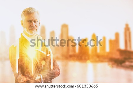 Double exposure of senior businessman in front of the big city #601350665