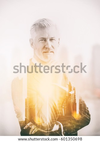 Double exposure of senior businessman in front of the big city #601350698