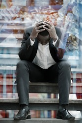 Double exposure of Serious African businessman professional failed or upset in his job and sitting on staircase with Covid-19 or corona virus positive test. Business problem concept.
