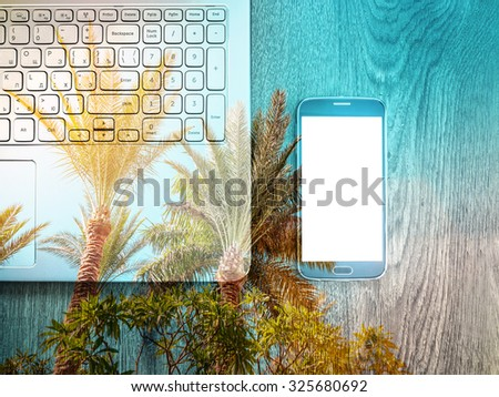 Double exposure of smartphone with Blank screen with laptop on table. Palms on background. Wooden texture