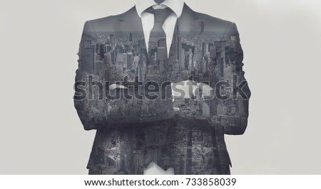Double exposure of success business man with arms crossed and city in background.
