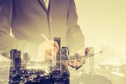 Double exposure of success businessman using digital tablet with city landscape background