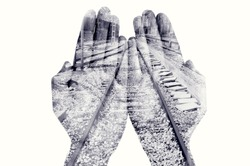 double exposure of the palms of a man put together and a railway, in black and white