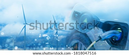 Double exposure of vehicle electric car charge battery with wind turbine and blue sky blur bokeh cityscape on panoramic background. Idea nature electric energy generate electricity. Green eco concept.