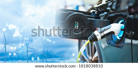 Double exposure of vehicle electric car charge battery with wind turbine and blue sky blur bokeh on panoramic background. Idea nature electric energy to generate electricity. Green energy eco concept. Stockfoto ©