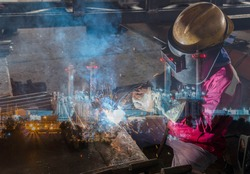 Double exposure of welder are welding a steel structure work with process Flux Cored Arc Welding(FCAW)and dressed properly with personal protective equipment(PPE)for safety with power plant background