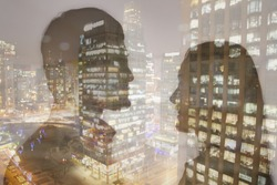 Double exposure of young couple over night cityscape
