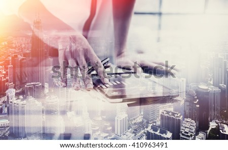 Double exposure photo.Female hand touching modern tablet.Investment manager working new private banking project office.Using electronic device.City skyscrapers background,film and bokeh effect.